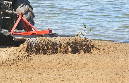 Tractor with large metal rake attached sifting, raking and clearing debris at a public beach in early morning