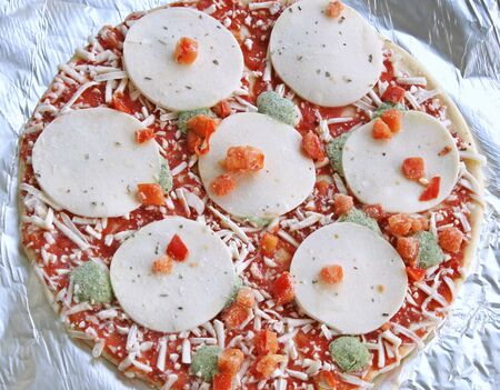 Frozen thin crust pizza with mozzarella cheese and veggies on aluminum foil ready for cooking