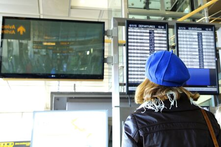 girl in beret looking at airport flight information board
