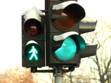regulating: green signal on traffic lights covered with snow