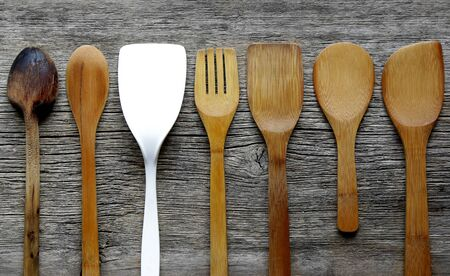 vintage kitchen spatulas and spoons on  board with one standing out from the crowd