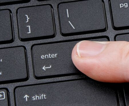transfering: computer enter key with finger pressing button on white background