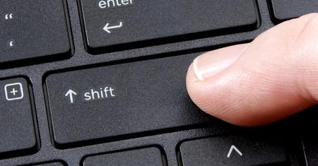 Tecla de mayúsculas equipo con el dedo presionando el botón en el fondo blanco Foto de archivo - 39559561