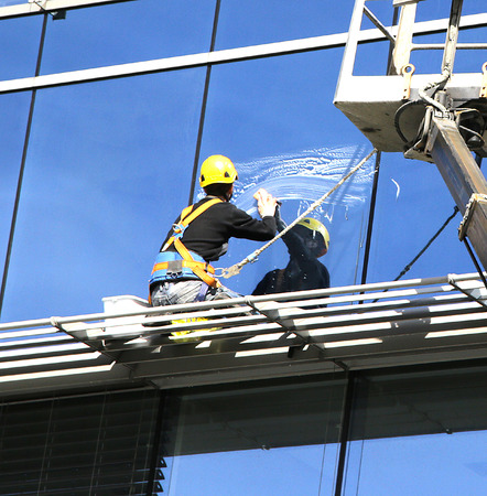 worker in helmet washing office building windows on sunny day