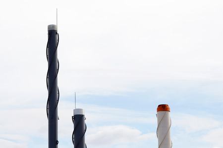 group of three industrial chimneys on sky background photo