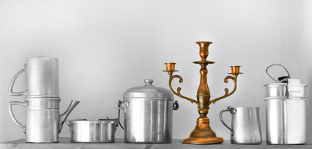 multiple personality: vintage kitchenware and candlestick on  board with one standing out from the crowd