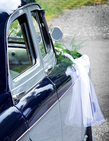 white ribbon: shining wedding car with bouquet and white ribbon