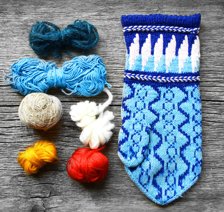 collectives: teamwork colored yarn balls making mittens on board background Stock Photo