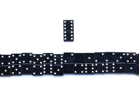 valuable: one vintage most valuable domino leader leading crowd of other dominoes isolated on white