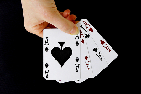 four of a kind: croupier player holding in hand card ace of spades four of a kind on black background