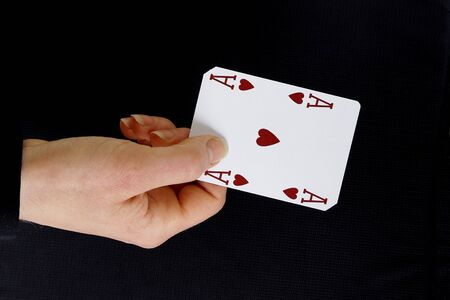 ace of hearts: an ace up your sleeve on black background showing hearts Stock Photo