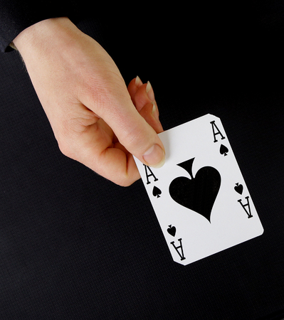 ace of spades: croupier player holding in hand card ace of spades on black background Stock Photo