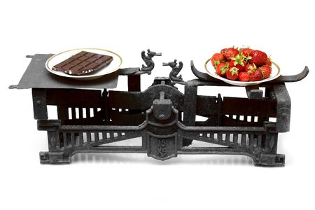 prior: strawberries and chocolate on different cups of vintage scales showing healthy food prior important that unhealthy sweets