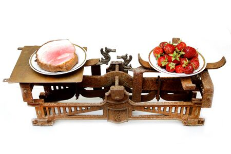 fat kid: strawberries and fat ham on different cups of vintage scales showing healthy food prior important that pork