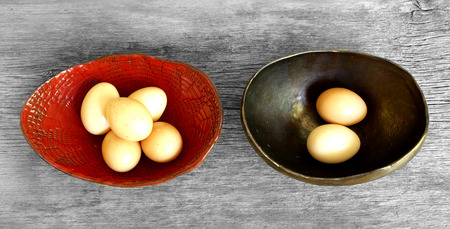 financial diversification: dont put all eggs in one basket proverb representing two trays with eggs shared Stock Photo