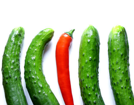 1 and crowd: green cucumbers with one red hot chili pepper standing out from the crowd Stock Photo