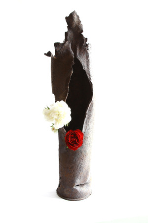 projectile: vintage rusted bomb shot projectile shell world war II explosed with flowers in hole on white