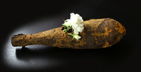 projectile: vintage rusted aviation bomb shot projectile shell world war II exploded with flowers in hole on black table