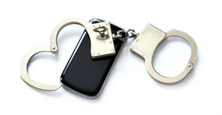 locked up: computer hacker smartphone and hand cuffs locked up on white table Stock Photo