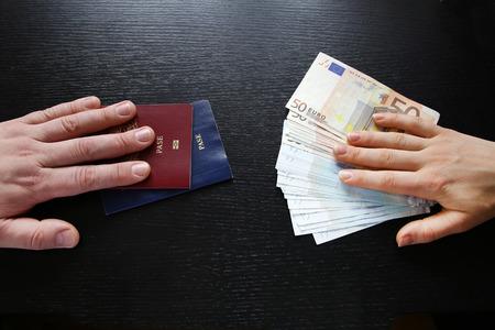 Comprar pasaporte extranjero ilegal manos el intercambio de dinero y documentos comprador vendedor Foto de archivo - 47737838