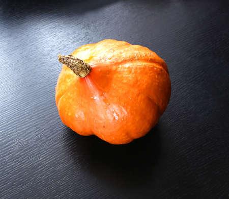 shiny black: orange pumpkin raw fresh shiny on black Stock Photo