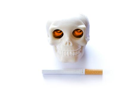 kills: smoking kills vintage human skull with burning lighted eyes and cigarette on white background