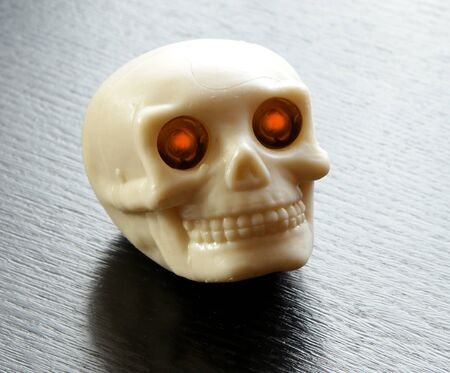 lighted: vintage human skull with burning lighted eyes on black table