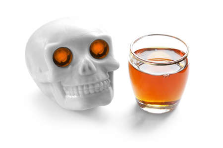 lighted: alcohol kills vintage human skull with burning lighted eyes and whiskey shot on white background