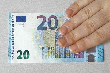 20 euro: hand holding new twenty 20 euro banknote greenback paper money issue 2015 obverse reverse