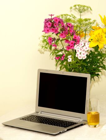 saturday evening feeling with juice flowers and laptop on table 스톡 콘텐츠