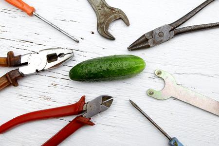 zeg of het niet is gebroken, maak het niet metafoor met hele komkommer en gereedschap Stockfoto