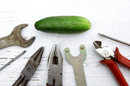 saying if it aint broke, dont fix it metaphor with whole cucumber and tools Stock Photo