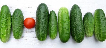 Tomate rojo entre pepinos verdes diciendo que se destaca del proverbio de la multitud Foto de archivo - 85099473