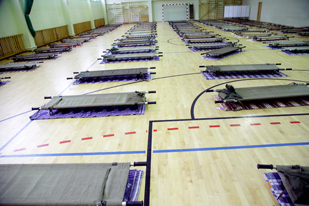 refugee camp in school sports hall full with stretcers