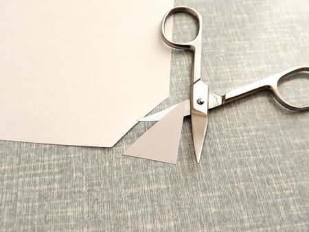 Cutting corners idiom Briticism hand takes sheet of paper and cutting corners by scissors doing something so easily and cheaply as possible 스톡 콘텐츠