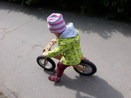 Small girl kid riding on bicycle pushing away by legs on pavement smiling sunny day laughter in park