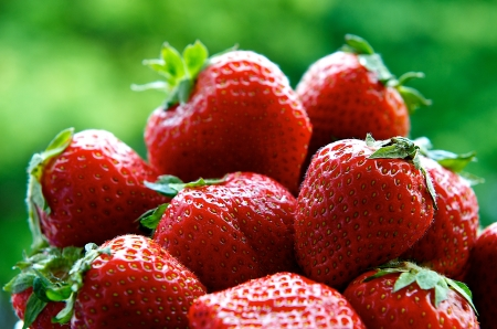 Fresh and smell red strawberries in blur green background, fragment view, a lot of strawberries close up