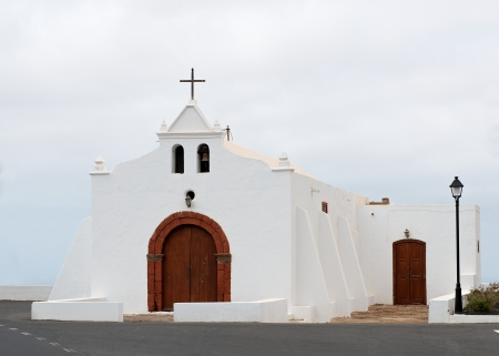 Small white church in the blue clear sky background in lanzarote, Europe photo