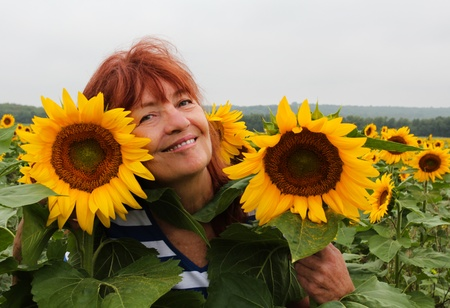 Close-up of a happy, smiling woman surrounded by sunflowers  photo