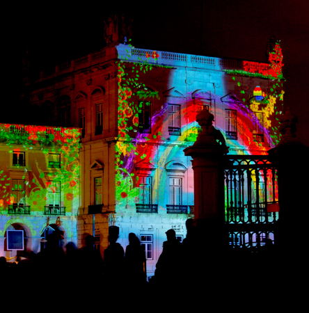Video Mapping in a building wall with silhouetted people watching.