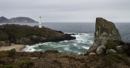 A lighthouse sits at the edge of the rocky shore on a stormy day.