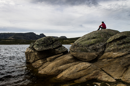 A man contemplates a lake while seated on a big rock.