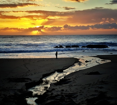Man Contemplates the Sunset at the Beach with a water stream coming from the ocean.