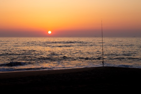 A fishing pole is silhouetted by the sunset at the beach.