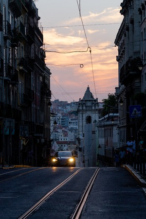 A car approaches in a tight street i n Lisbon just after sunset.