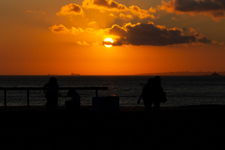 A few silhouetted people walk along a pier during sunset.