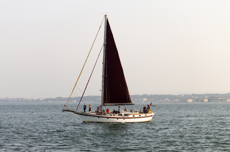 A sailboat passes by in the river with several people on board. Banco de Imagens