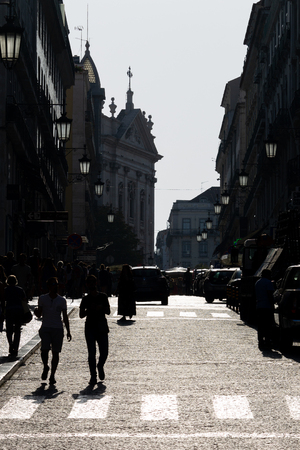 SIlhouetted people walking down a street in Lisbon.