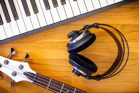A wooden background with a set of musical instruments consisting of a keyboard, a bass guitar and a pair of headphones.