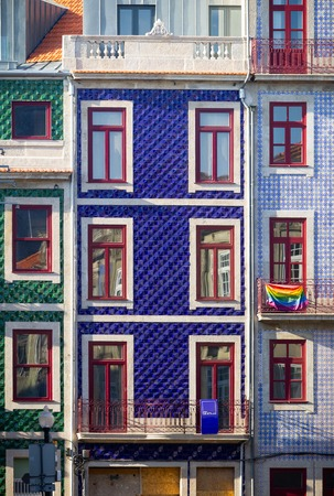An LGBT flag hangs on a balcony from a building with a tiled facade.